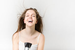 Beautiful smiley young girl blow drying her hair. Portrait of a beautiful smiley young girl blow drying her hair Royalty Free Stock Photo