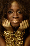 Beautiful smiling african american woman in gold accessories with arms crossed under her chin Stock Images