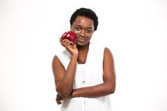 Beautiful smiling african american woman standing and holding red apple Stock Photography