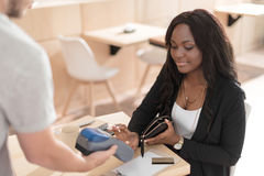 Smiling african american woman paying with credit card through terminal in cafe royalty free stock photography