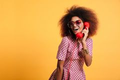 Beautiful smiling african woman in dress posing with retro phone Stock Images