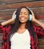 Beautiful smiling african woman with headphones enjoying listens music in city Royalty Free Stock Image
