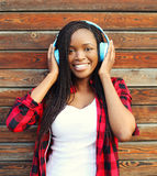 Beautiful smiling african woman with headphones listens to music Royalty Free Stock Images