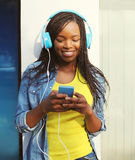 Beautiful smiling african woman with headphones listens to music Royalty Free Stock Photography