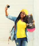 Beautiful smiling african woman with skateboard taking self-portrait picture on smartphone Stock Photos
