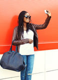 Beautiful smiling african woman taking self-portrait picture on smartphone in city. Wearing a leather jacket and bag over red background Stock Image
