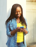 beautiful smiling african woman using smartphone in city Stock Image