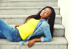 Beautiful smiling african woman wearing a jeans clothes on stairs Stock Photos