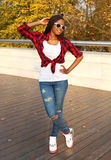 Beautiful smiling african woman wearing a sunglasses, red checkered shirt posing Royalty Free Stock Photos