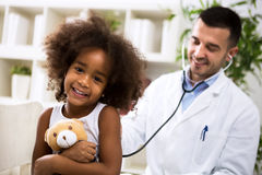 Beautiful smiling afro-american girl with her pediatrician Stock Images