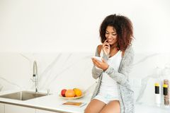 Beautiful smiling afro american woman texting on mobile phone Stock Image