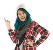 Beautiful smiling and amazed girl pointing upward. On white background. Pierced, turquoise haired and dressing up a plaid shirt Royalty Free Stock Image