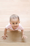 Beautiful smiling asian baby girl while crawling up a stair. Royalty Free Stock Images
