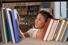Asian female student with books. Beautiful smiling asian female student looking at books on bookshelf Stock Photo