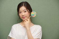 Lovely girl. Beautiful smiling Asian girl with colorful lollipop Stock Images