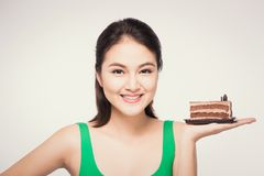 Beautiful smiling asian young woman with a chocolate cake on white background royalty free stock image