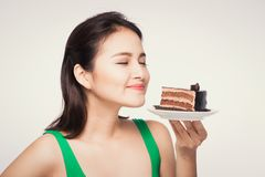 Beautiful smiling asian young woman with a chocolate cake on white background stock images