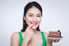 Beautiful smiling asian young woman with a chocolate cake isolated on white background royalty free stock photos