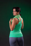 Beautiful smiling athletic, fitness woman standing, posing with a towel on a gray background with a green backlight Stock Photos