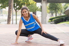 Beautiful smiling athletic woman doing stretches before training Stock Images