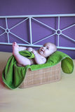 Beautiful smiling baby boy sitting in basket with green blanket in purple interrior Royalty Free Stock Images