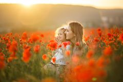 Beautiful smiling baby girl with mother are having fun in field of red poppy flowers over sunset lights, spring time. Beautiful happy couple mother and cute royalty free stock photography