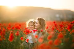 Beautiful smiling baby girl with mother are having fun in field of red poppy flowers over sunset lights, spring time. Beautiful happy couple mother and cute stock photography