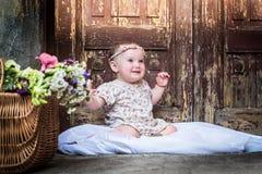 Beautiful Smiling Baby Girl. Portrait of beautiful smiling baby girl on the background of the vintage old door. Close-up stock photo