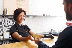 Smiling barista taking payment from client at counter of a coffee shop. Beautiful smiling barista taking credit card from customer to pay for beverage at coffee Royalty Free Stock Images