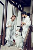 Beautiful smiling beaming contended couple petting a beautiful white dog. Family mornings with a dog. Beautiful charming smiling beaming contended couple in home stock photos