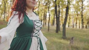 Beautiful smiling big model with bright red hair in a national light simple dress in green and white color whirl in the. Autumn forest, pretty girl poses for stock video footage