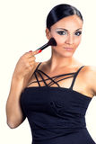 Beautiful smiling black hair girl applying makeup with brush Stock Photo