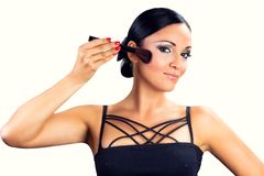 Beautiful smiling black hair girl applying makeup with brush Royalty Free Stock Image
