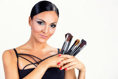 Beautiful smiling black woman girl holding makeup brushes. Stock Photography