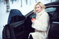 Beautiful business woman in luxurious white fur coat drinking hot coffee on snowy winter day sitting in her car. Beautiful smiling blond business woman with Royalty Free Stock Photos