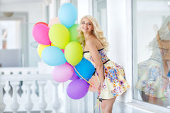 Beautiful smiling blond girl with colorful balloons Stock Photos