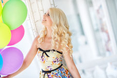 Beautiful smiling blond girl with colorful balloons Stock Images