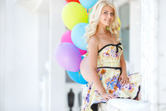 Beautiful smiling blond girl with colorful balloons Royalty Free Stock Photo