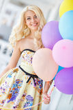 Beautiful smiling blond girl with colorful balloons Stock Photography