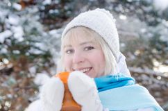 Beautiful smiling blond girl in a sport hat holding a cup of hot tea stock images