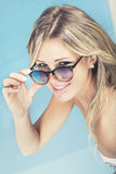 Beautiful smiling blonde hair girl with sunglasses in the pool. Stock Image
