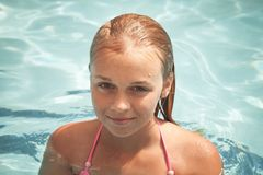 Beautiful smiling blond girl swims in a pool Royalty Free Stock Photos