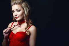Beautiful smiling blond model with perfect make up and scrapped back hair wearing red corset strapped top and choker stock images