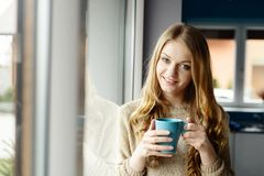 Beautiful smiling blond woman drinking coffee by the window Royalty Free Stock Images