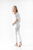 Beautiful smiling blond woman in white blouse and pants on white background Royalty Free Stock Image