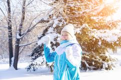 Beautiful smiling blonde girl playing snowballs in sunny day stock photography