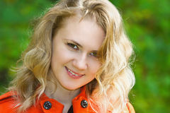 Beautiful smiling blonde girl in the red coat Stock Photos