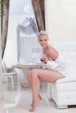 Beautiful smiling blonde posing sitting on sofa stock photo