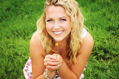 Beautiful smiling blonde woman on the green meadow. Royalty Free Stock Photos
