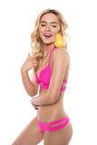 Beautiful smiling blonde woman in pink swimsuit pointing at pear Stock Images